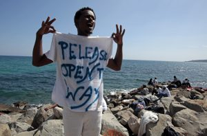 """A migrant shouts a slogan as he wears a Tee Shirt with the message, """"Open The Way"""" as he stands on the seawall at the Saint Ludovic border crossing on the Mediterranean Sea between Vintimille, Italy and Menton, France, June 14, 2015. On Saturday, some 200 migrants, principally from Eritrea and Sudan who attempted to cross the border, were blocked by Italian police and French gendarmes. REUTERS/Eric Gaillard - RTX1GG1X"""